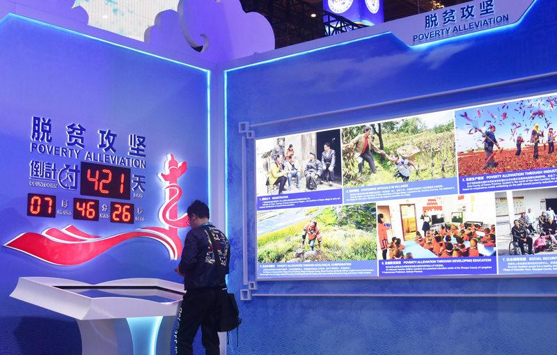 2019年11月6日,观众在第二届进博会中国馆脱贫攻坚倒计时显示屏前参观。新华社记者 魏海 摄