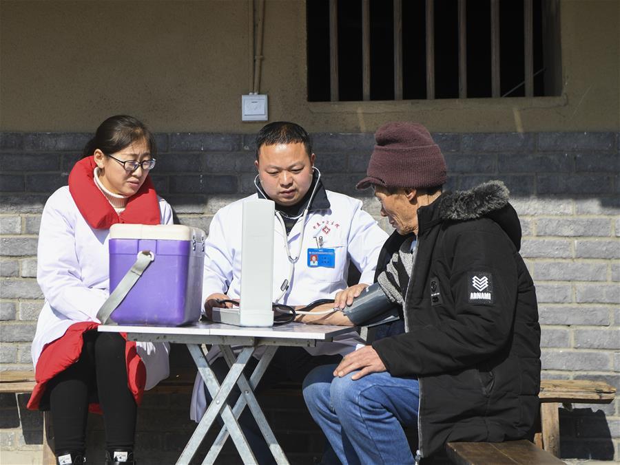 重庆市石柱土家族自治县中益乡卫生院的医护人员为华溪村村民谭登周测量血压(2019年12月10日摄)。新华社记者 王全超 摄
