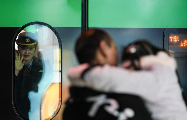 動車即將離開南昌西站站臺,車內的卞菁(左)向丈夫和女兒告別。新華社記者胡晨歡攝