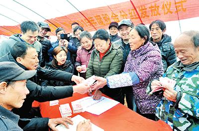 江西鄱阳县四十里街镇塘湖村蔬菜大棚基地,贫困户领到产业扶贫分红,笑逐颜开。