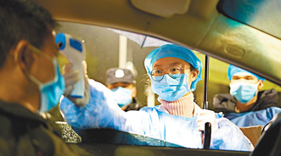 在广西来宾市某高速公路出口,医护人员为司机监测体温。 高如金摄(人民视觉