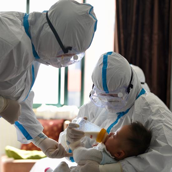 """""""临时妈妈""""章晓燕(左)和王四妹(右)给醒来的孩子喂奶"""