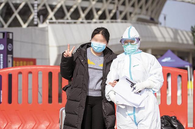 3月10日,武漢市江夏方艙醫院醫護人員與治愈者合影留念(圖片來源:湖北日報)
