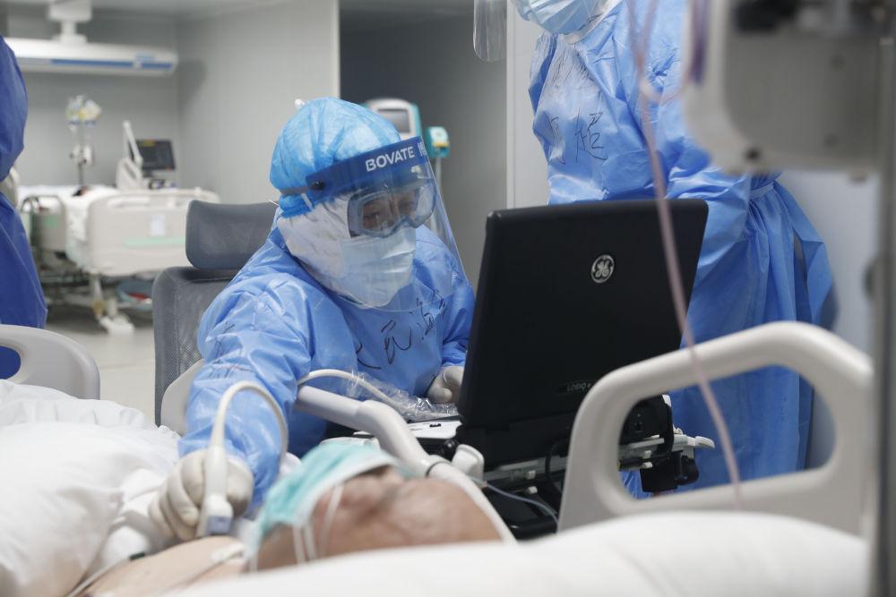 在武汉火神山医院重症监护室内,重症医学一科副主任李文放为患者诊治(2月24日摄)。新华社发(吴浩宇 摄)