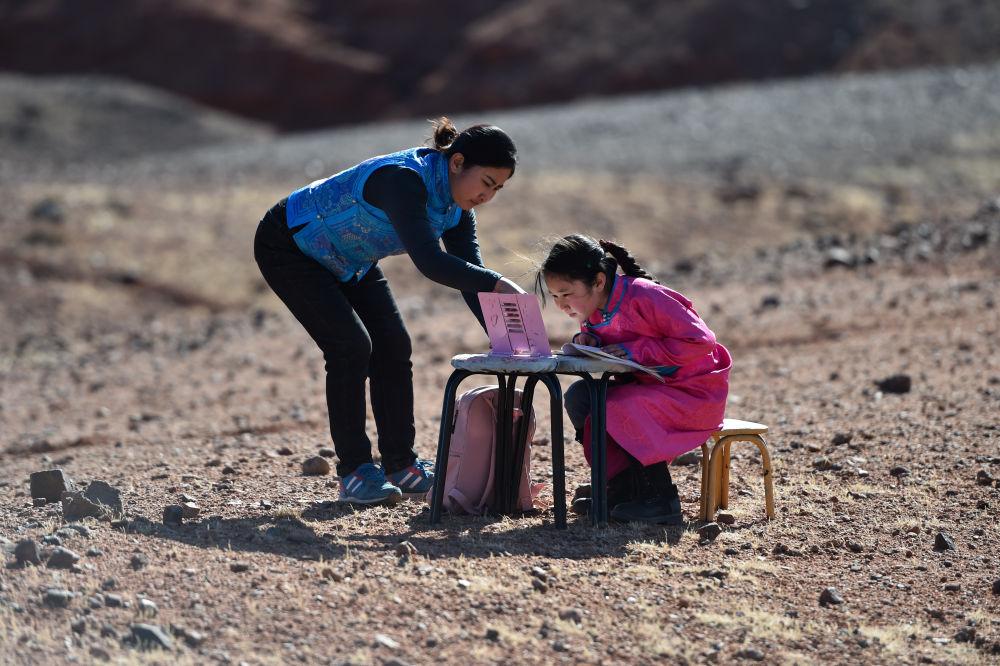9岁的策耿(右)在家附近的戈壁上上网课(4月1日摄)。策耿是内蒙古自治区阿拉善左旗蒙古族学校四年级学生。由于疫情防控,策耿父母长期雇佣的一名外省羊倌没能回到当地,一家人只好回到阿拉善左旗乌力吉苏木温都尔毛道嘎查的牧区家中照看羊群。期间,策耿一边协助父母,一边上网课。新华社记者 刘磊 摄