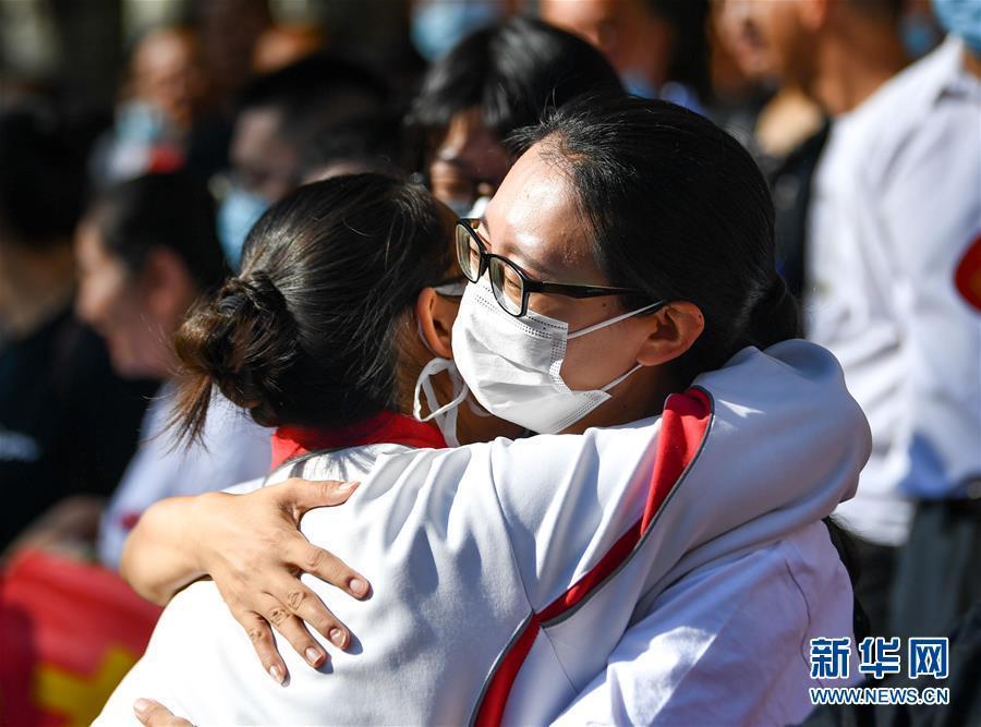 7月7日,老師(右)在呼和浩特市第二中學考點外擁抱即將參加高考的考生。 (新華社)