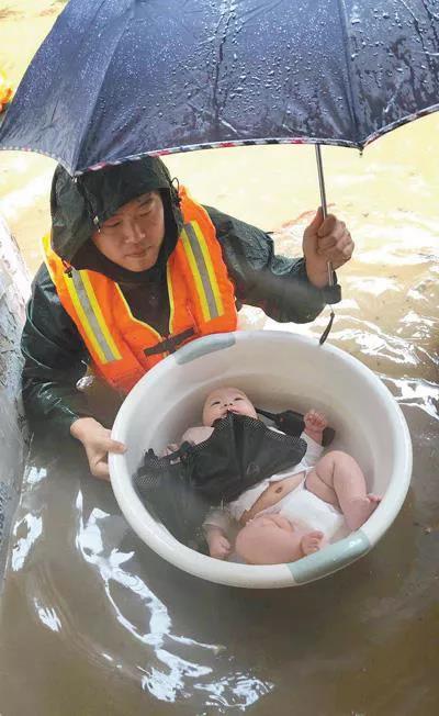 图为2020年6月27日,在宜昌市伍家岗区,消防员用水盆将3个月大的婴儿安全转移。 人民视觉  王方/摄