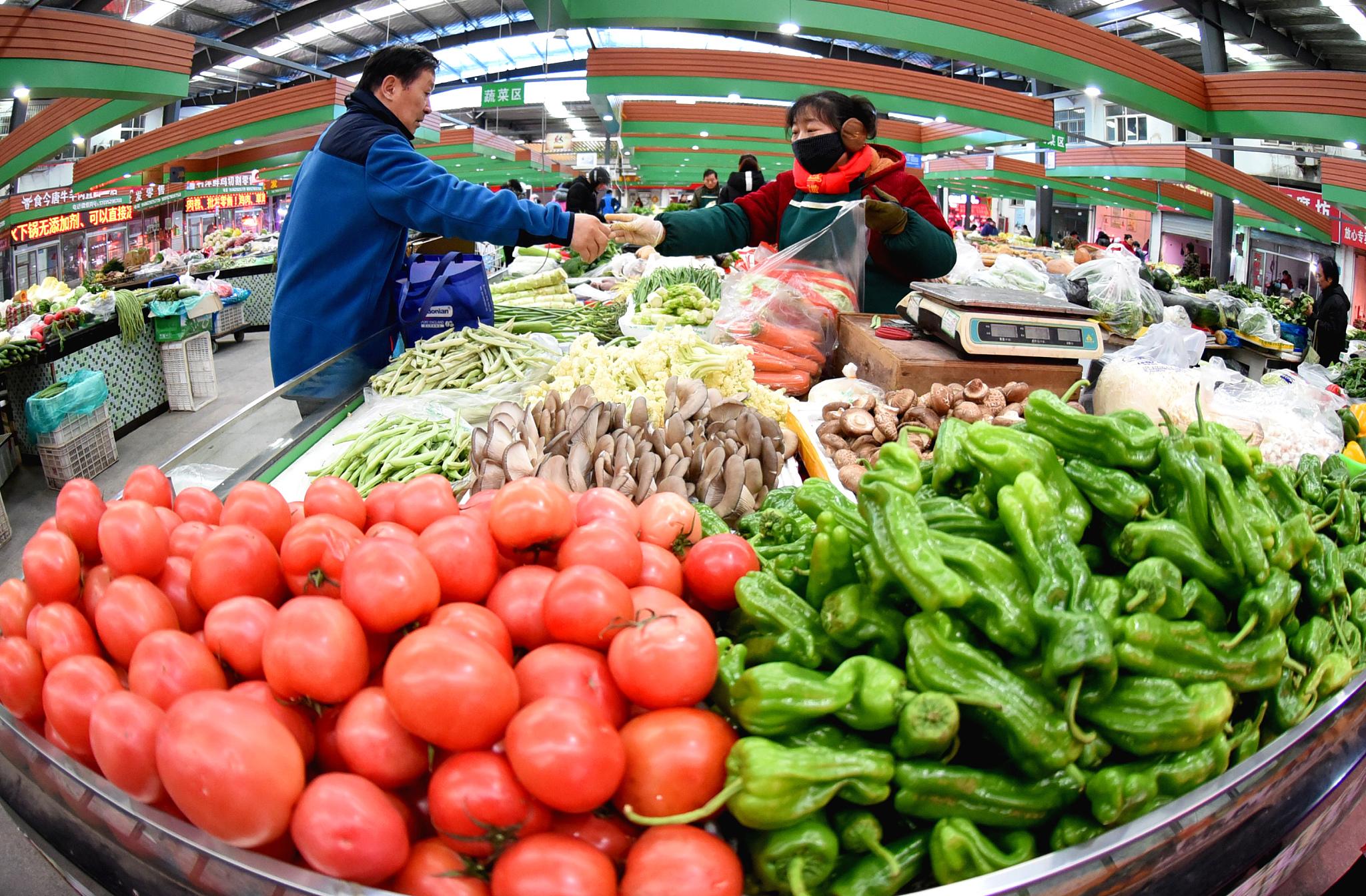 2020年12月9日,居民在江苏连云港市海州区一家农贸市场选购蔬菜。