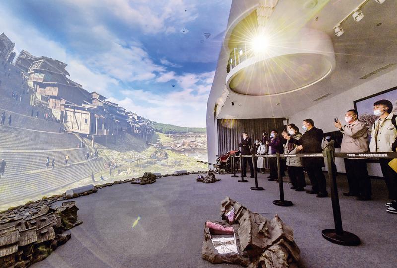 """近年来,重庆红岩革命纪念馆以新技术把革命文物搬上屏幕和舞台,创新革命文物展示,让红岩革命文物""""活""""起来。图为在重庆红岩革命纪念馆""""红岩记忆""""数字体验厅内,观众们观看以双曲三维穹幕技术展示的场景。 新华社记者 李贺/摄"""