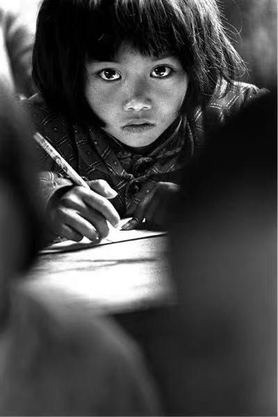 """△1991年,摄影师解海龙在安徽省金寨县张湾小学拍摄的刻苦学习的苏明娟,成为希望工程的形象代表。人们将她称为""""大眼睛女孩""""。"""