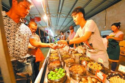 游客在台湾美食街品尝特色小吃