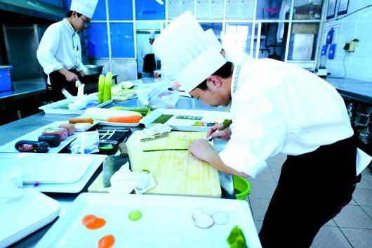 淄博机电工程学校学生在中餐烹饪实训基地练习雕刻.
