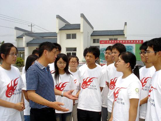这是2009年,沈浩(前左二)与在小岗村进行社会实践的大学生交谈。新华社发