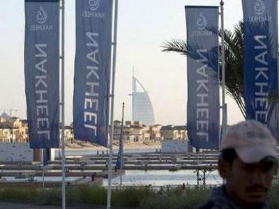 Nakheel company flags fly on Palm Jumeirah with Burj Arab in the background in Dubai December 14, 2009.REUTERS/Steve Crisp