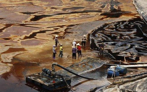 Workers dispose of acidic copper wastewater at a sewage pit in Zijinshan bio-hydrometallurgical copper plant of Zijin Mining Group, Shanghang county, East China's Fujian province, July 13, 2010. The leak of 9,100 cbm of acidic water has plagued Tingjiang, a major river in eastern Fujian and is shedding light on the fragility of China's ecological system due to accelerated industrialization.[Photo/CFP]