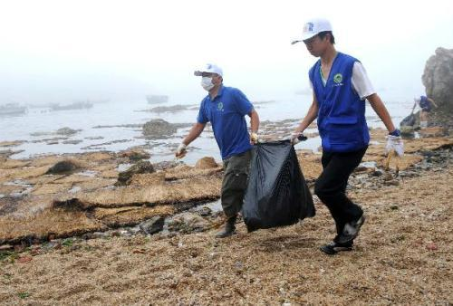 Volunteers clean up the spilled oil on a beach in Shicao Village of Dalian, northeast China's Liaoning Province, July 21, 2010. Volunteers from Dalian Environment Protection Volunteer Association joined in clean-up work of spilled crude oil caused by the oil pipeline explosion occurred on July 16 in Dalian. (Xinhua/Li Gang)