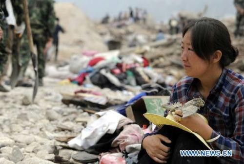 Hui Guoqin holding her father's belongings waits on ruins and wish for the good news of her missing parents and sister-in-law in the landslides-hit Zhouqu County, Gannan Tibetan Autonomous Prefecture in northwest China's Gansu Province, Aug. 11, 2010. The death toll in the massive mudslide in Zhouqu has risen to 1,117, with 627 still missing, local authorities said Wednesday. (Xinhua/Tao Ming)