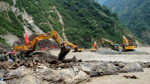 Cranes are used to finish repairing the last part of a landslide-hit road in Mianzhu City, southwest China's Sichuan Province, Aug. 22, 2010.  (Xinhua/Wang Ping)