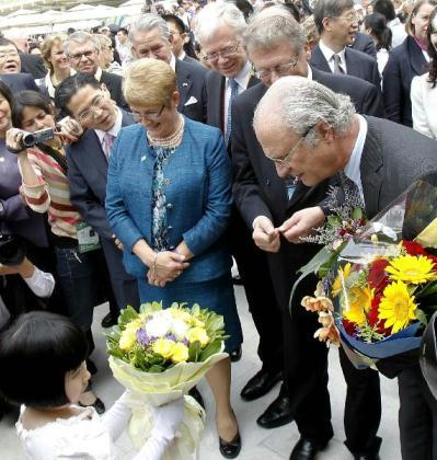Swedish King Carl XVI Gustaf (R, front) receives flowers during his vitit to the Sweden Pavilion at the World Expo park in Shanghai, east China, May 23, 2010, the National Pavilion Day for Sweden. (Xinhua/Liu Ying)