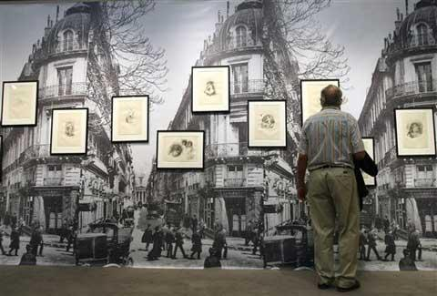 A man looks at sketches, parts of the Vollard collection that will be sold at auction, Tuesday June 29, 2010, in Paris.