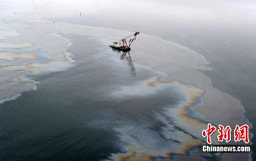 A dark brown belt of crude oil, can be seen stretching at least 50 square kilometers in waters off Xingang Harbor.