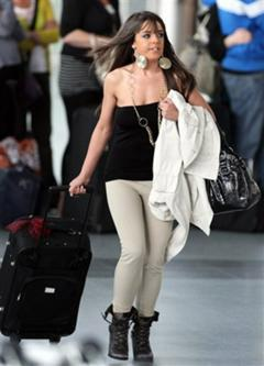 A woman rushes to catch her flight, after some flights were canceled due to the volcanic ash cloud, at Newcastle International Airport, England, Sunday May 16, 2010. Civil aviation officials say a drifting, dense cloud of volcanic ash is encroaching on British airspace, forcing the closure of airports in Northern Ireland, Scotland, and much of England. (AP Photo/Scott Heppell)