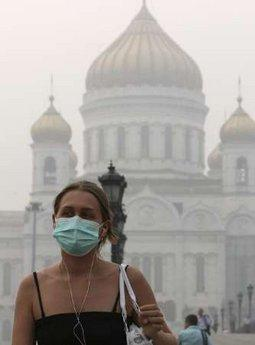 A woman wearing a protective mask walks in front of Christ the Saviour Cathedral seen in the background amid heavy smog in Moscow, August 4, 2010. Airquality levels in Moscow tumbled to an eight-year low on Wednesday as the Russian capital was blanketed in thick smoke from forest and peat fires, said Moscow's state agency for monitoring air pollution. REUTERS/Stringer