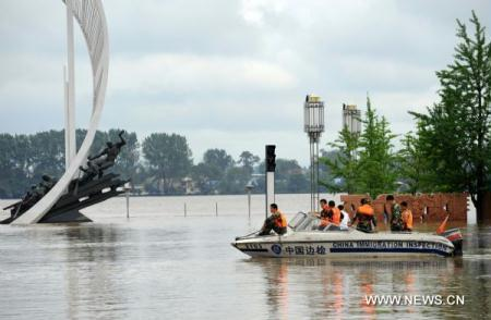 Soldiers steer a boat for a rescue operation along the Yalu River in Dandong City, northeast China's Liaoning Province, Aug. 21, 2010. Heavy rains hit Dandong from Aug. 19 to 21, causing flood around the area.(Xinhua/Reng Yong)