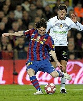 Barcelona's Argentinian forward Lionel Messi (L) vies with Valencia's defender Angel Dealbert (R) during their Spanish League football match between Barcelona and Valencia at Camp Nou stadium in Barcelona. Messi scored a sensational hat-trick to take his season's tally to 22 goals as Barcelona returned to the top of the Spanish Primera Liga with a 3-0 home victory over 10-man Valencia on Sunday.(AFP/Lluis Gene)