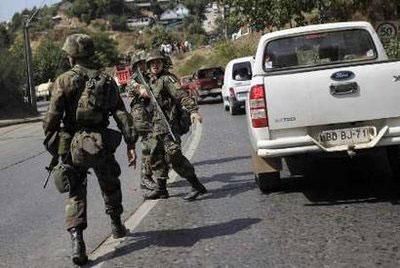 Chileansoldierstrytomaintainorderasresidentsdrivehurriedlyawayfromthecoasttohighergroundafteratsunamiwarningwasissuedfollowingastrongaftershock,inConstitucion,March3,2010.REUTERS/IvanAlvarado