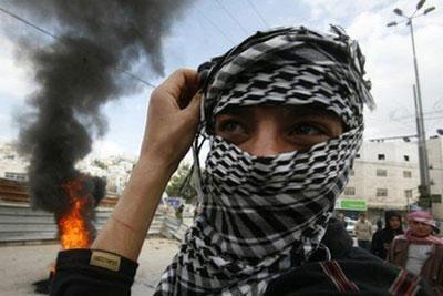 AmaskedPalestiniandemonstratorstandsnearburningtiresduringclasheswithIsraeliforcesintheWestBankcityofHebron.(AFP/HazemBader)