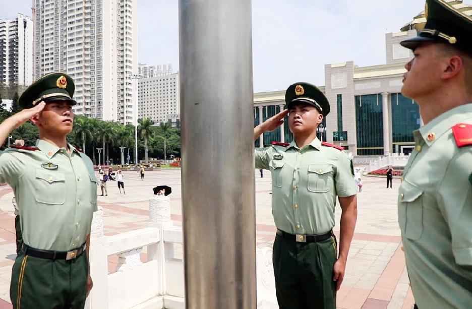 国旗班战士向国旗敬礼。董亚涛摄