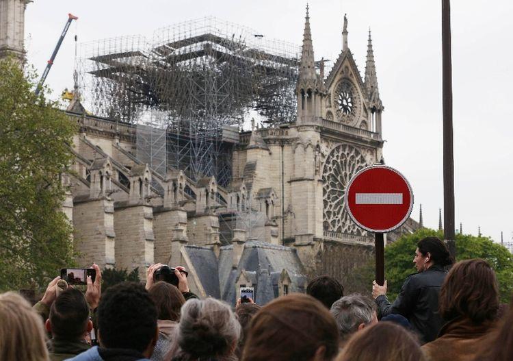 """2019年4月16日,在法国巴黎,人们聚集在""""受伤""""的巴黎圣母院附近。(新华社记者高静摄)"""