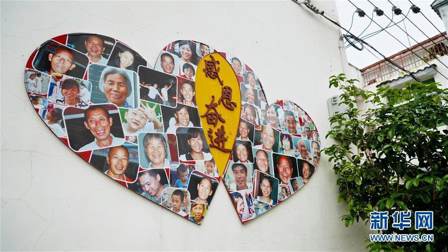 这是5月7日拍摄的江西瑞金华屋村内的照片墙。 新华社记者 胡晨欢 摄
