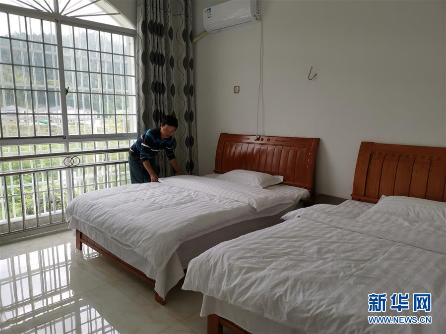 在浏阳市张坊镇田溪村,贫困户罗铿在整理客房,他依托自己的房子开办民宿(5月9日摄)。 新华社记者 刘良恒 摄