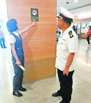 市卫生计生监督机构执法人员在公共场所进行禁烟标识检查。