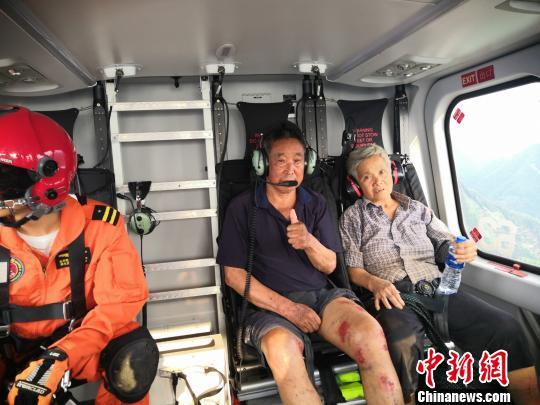 曲降机告急救济两名受灾大众 。  钟欣 摄
