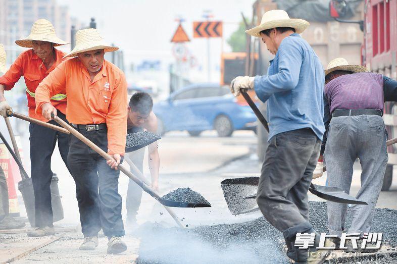 施工职员踩着滚烫的沥青 , 对门路两侧便讲停止沥青摊展 。