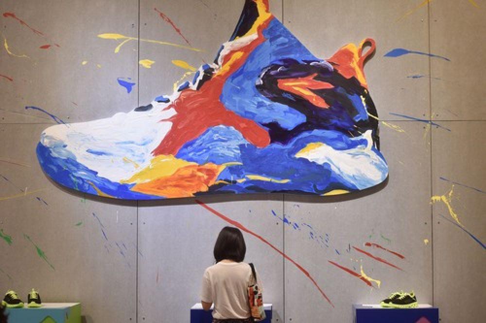 客商在中国(晋江)国际鞋业暨国际体育产业博览会上了解安踏运动鞋(2017年4月18日摄)。(新华社记者宋为伟 摄)