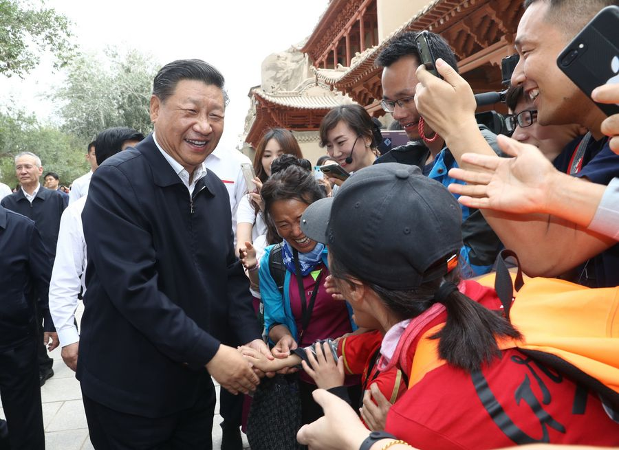 Chinese President Xi Jinping, also general secretary of the CPC Central Committee and chairman of the Central Military Commission, visits the Mogao Grottoes in Dunhuang, a key cultural heritage site under state-level protection, during his inspection tour of northwest China
