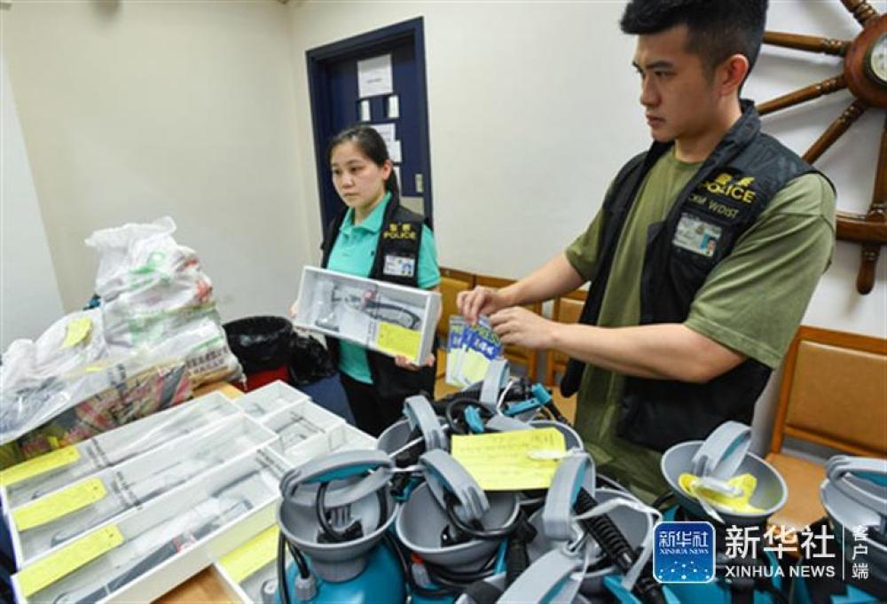 ↑9月1日,在港岛西区警署召开的记者会上,警方展示拘捕现场检获的斧头、记者证等证物。新华社记者 刘大伟 摄