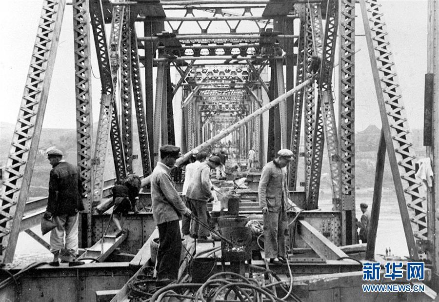 修建成渝铁路的工人们在紧张地架设沱江大桥(资料照片)。  新华社发