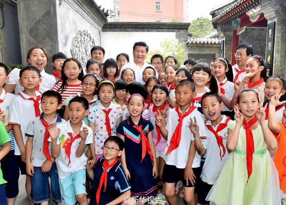 """2014年5月30日,习近平总书记来到北京市海淀区民族小学,参加庆祝""""六一""""国际儿童节活动。这是活动结束后,习近平与学校师生合影留念。(新华社)"""