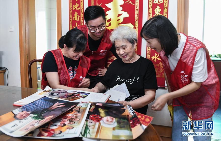 83岁的劳模教师顾月英(右二)向志愿者们讲述当年的教师生涯(9月3日摄)。 新华社记者 徐昱 摄