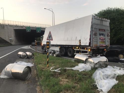 一辆载运化学物质的货车,载运的化学桶掉落到路面