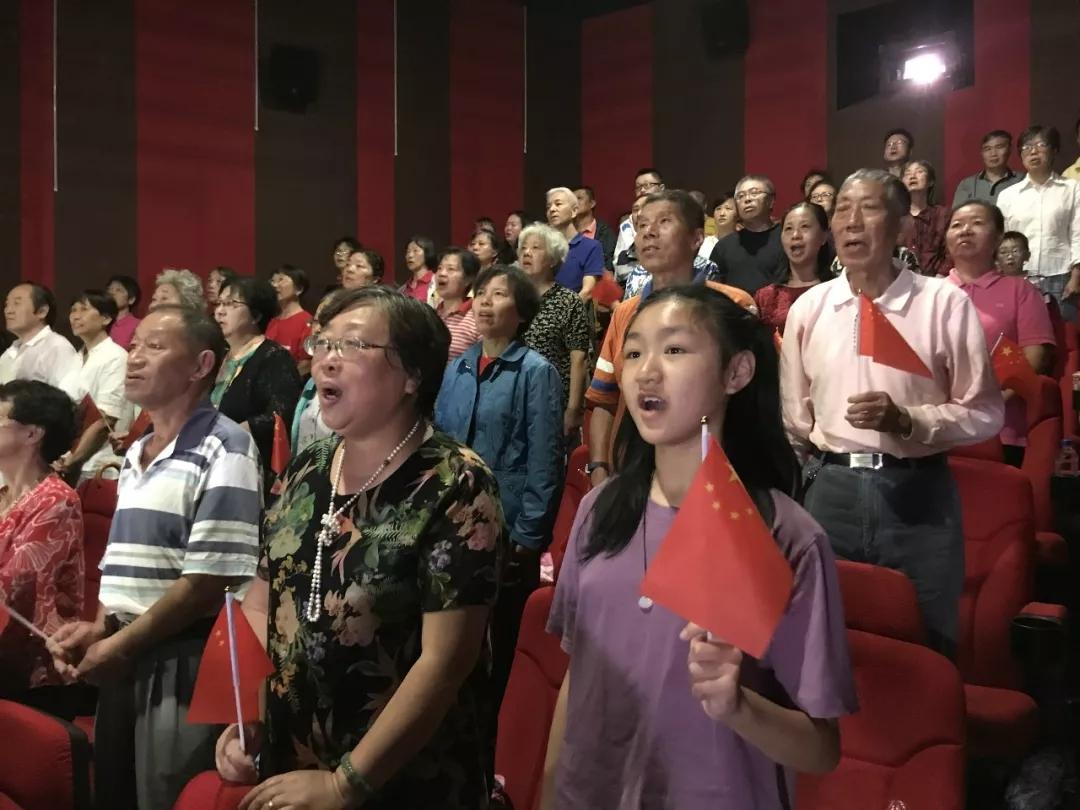 不雅众在上海某片子院不雅看盛典,共唱国歌。