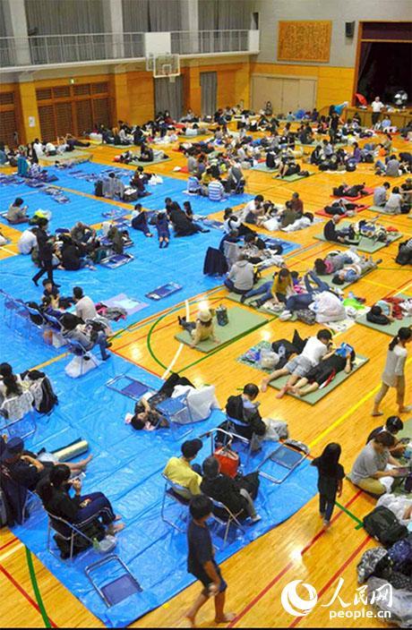 12日傍晚,神奈川县厚木市相模川附近居民前往市立厚木中学体育馆避难。(图片来源:日本《朝日新闻》网站)