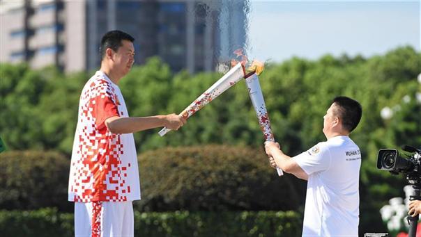 8月1日,火炬手王治郅(左)与火炬手肖东交接火炬。 新华社记者万象摄