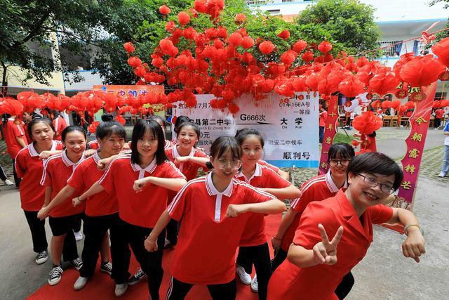 """7月5日,在广西柳州市融安县第二中学,老师和学生在""""顺利号""""动车票前合影。"""