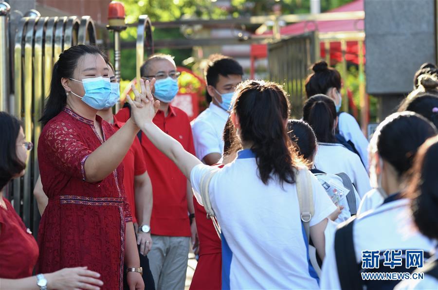 7月7日,在深圳市福田中学考点外,老师为即将参加高考的考生加油。 当日,2020年高考拉开帷幕。 (新华社)
